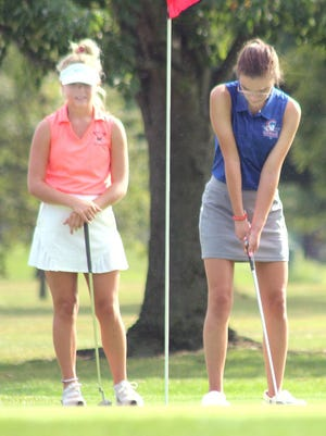 Moberly High School golfer Aubrey Rash looks to putt Tuesday at Kirksville Country Club while a Kirksville golfer stands to watch. The Lady Spartans golf team played its first event of the 2020 season that day finishing last out of four schools.