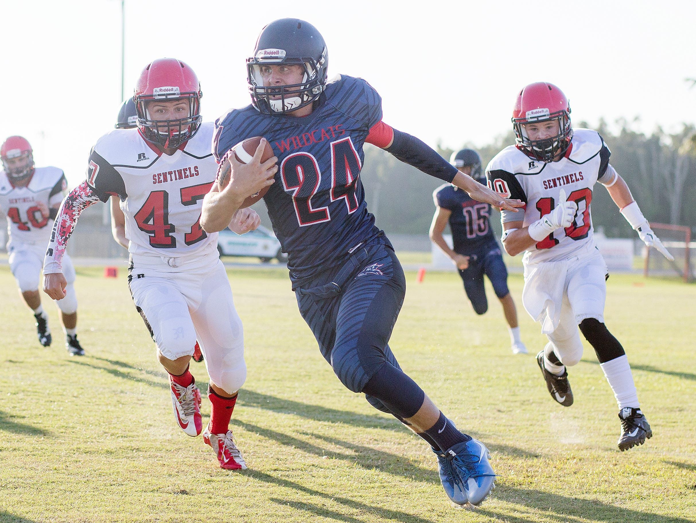 Estero High School's Max Bossi picks up a first down against Evangelical Christian School on Thursday at Estero High School.