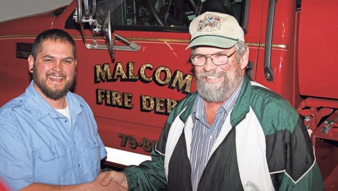 Malcom Volunteer Fire Department Chief Jake Dayton, left, thanks Malcom's Dave Steffen, right, for directing a $2,500 donation from America's Farmers Grow Communities, sponsored by the Monsanto Fund, to be donated to the Malcom Volunteer Fire Department