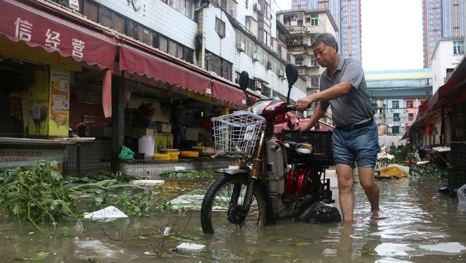 A man pushes a motorbike through a flooded street in Xiamen, in China's eastern Fujian province after Typhoon Meranti made landfall on Sept. 15, 2016, with winds up to 138 mph, knocking out electricity in some areas and causing rail delays.