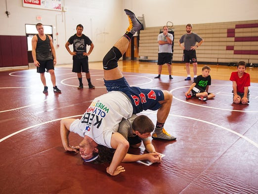 Olympian wrestler Jake Herbert demonstrates how to perform an assisted back bridge maneuver during a wrestling camp at Stuarts Draft High School on Wednesday, July 9, 2014.