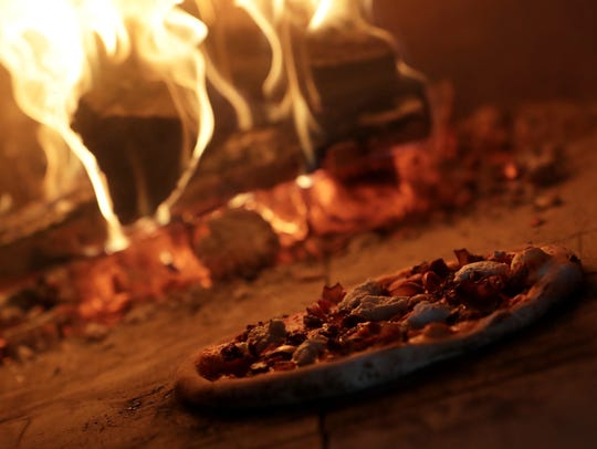 A sausage and peppers pizza is cooked in a 900-degree