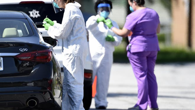 Medical workers get samples during drive-up COVID-19 testing at Fire Station 1 in Augusta, Ga., Friday morning June 5, 2020.