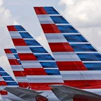 The tails of four American Airlines passenger planes parked July 17, 2015, at Miami International Airport, in Miami.