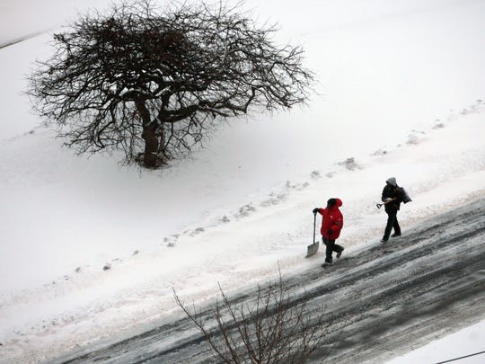 A couple of would be snow shovelers walk along Rumsey Road in Yonkers after the overnight snowfall, Jan. 27, 2015.