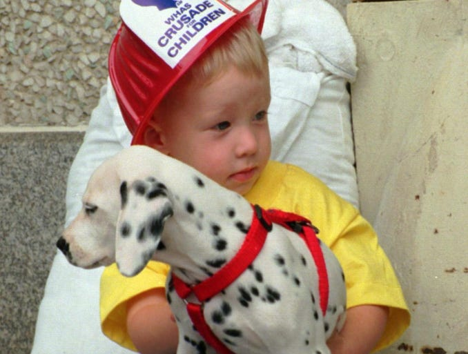 1996: Levi Hamilton, 2, snuggled up with a Dalmatian yesterday as he waited with the Flaherty Fire and Rescue Department of Meade County during the WHAS Crusade for Children yesterday.-