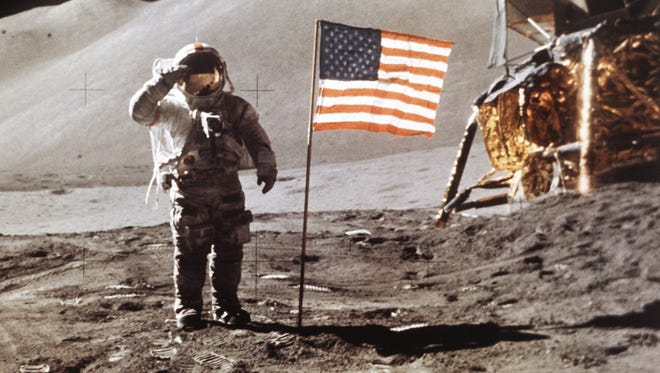 Apollo 15 Lunar Module Pilot James B. Irwin salutes while standing beside the fourth American flag planted on the surface of the moon on July 30, 1971.
