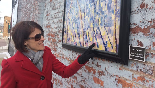 "Howell Main Street DDA Director Cathleen Edgerly examines a copy of the ""Icy Forest"" painting on display on the west outer wall of the Howell Opera House. The original painting sold for hundreds of dollars."