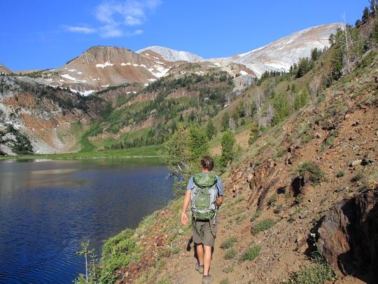 Andy Gonerka hikes around Ice Lake in the Wallowa Mountains' Eagle Cap Wilderness at the beginning of a climb up the Matterhorn, a 9,824 foot summit seen high above.