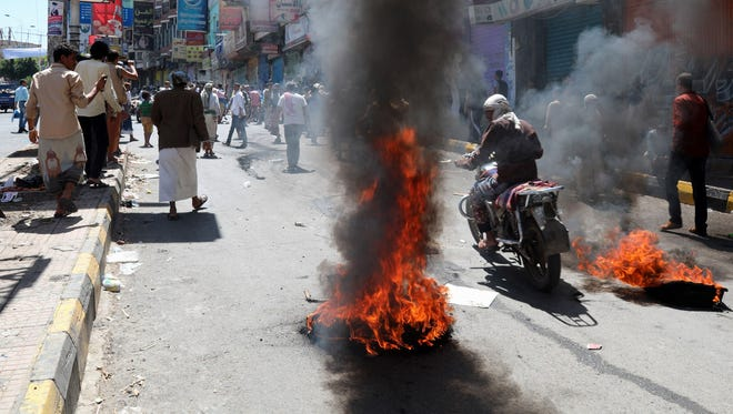 A Yemeni motorcyclist rides past burning tires in a street during a protest against inflation and the rise of living costs in the southwestern Yemeni city of Taez on Oct. 2, 2018. The UN Office for the Coordination of Humanitarian Affairs  warned last month that the currency depreciation was likely to make another 3.5 million Yemenis food insecure, in addition to 8.4 million people who already need emergency food assistance.