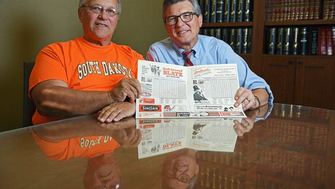 Don, left, and Doug Hajek pose for a portrait with a program from a 1960 baseball game between the Dodgers and the Braves in Los Angeles.