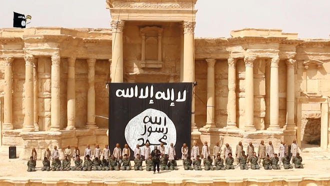 An image grab taken from a video made available by Jihadist media outlet Welayat Homs on July 4, 2015 allegedly shows 25 Syrian government soldiers kneeling in front of, what appears to be children or teenagers wearing desert camouflage, in the ancient amphitheatre in the city of Palmyra, ahead of being executed. The executions in the Palmyra amphitheatre were first reported on May 27 by the Syrian Observatory for Human Rights, a Britain-based monitor, less than a week after IS captured the city.