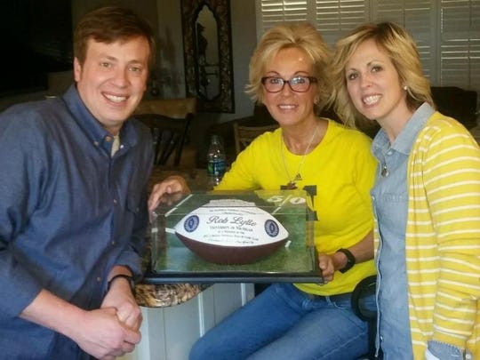 Rob Lytle's family, left to right, son Kelly, wife Tracy and daughter Erin, with the football congratulating Rob on his election to the College Football Hall of Fame in January 2015.