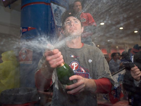 Chase Utley sprays champagne in the clubhouse following