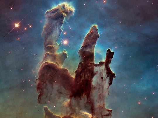 "This image made by the NASA/ESA Hubble Space Telescope shows the Eagle Nebula's ""Pillars of Creation."" The dust and gas in the pillars is seared by the intense radiation from young stars and eroded by strong winds from massive nearby stars. The Hubble Space Telescope marks its 25th anniversary. A full decade in the making, Hubble rocketed into orbit on April 24, 1990, aboard space shuttle Discovery.  (NASA,†ESA/Hubble, Hubble Heritage Team via AP) ORG XMIT: NY922"