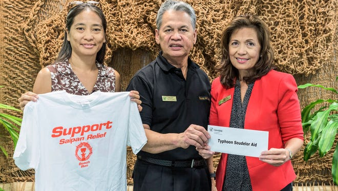 From left, Myra Macapagal, Jackie Marati, Ben Pablo take a photo during the check presentation for Saipan relief efforts.