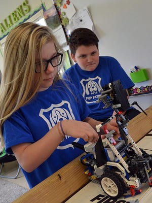 Carsen Flowers, left, and Bennett Ciaravino work together with their robot, Murphy, as they prepare for the upcoming FIRST LEGO League World Championships to be held in Houston, Texas on April 19-22.
