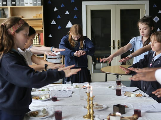 Students bless candles during a traditional Seder meal at The Good Shepherd Catholic Montessori School in Madison Place on Tuesday, April 15, 2014.  Principal Dan Teller lead several small groups of primary students in the meal, and taught them about the significance of Passover and the food they ate.  The schools does this every year as a part of a practice of living their lessons.  After studying Passover for the past several weeks, they celebrated the traditional Seder meal and connected it to Jesus' last meal with his disciples.
