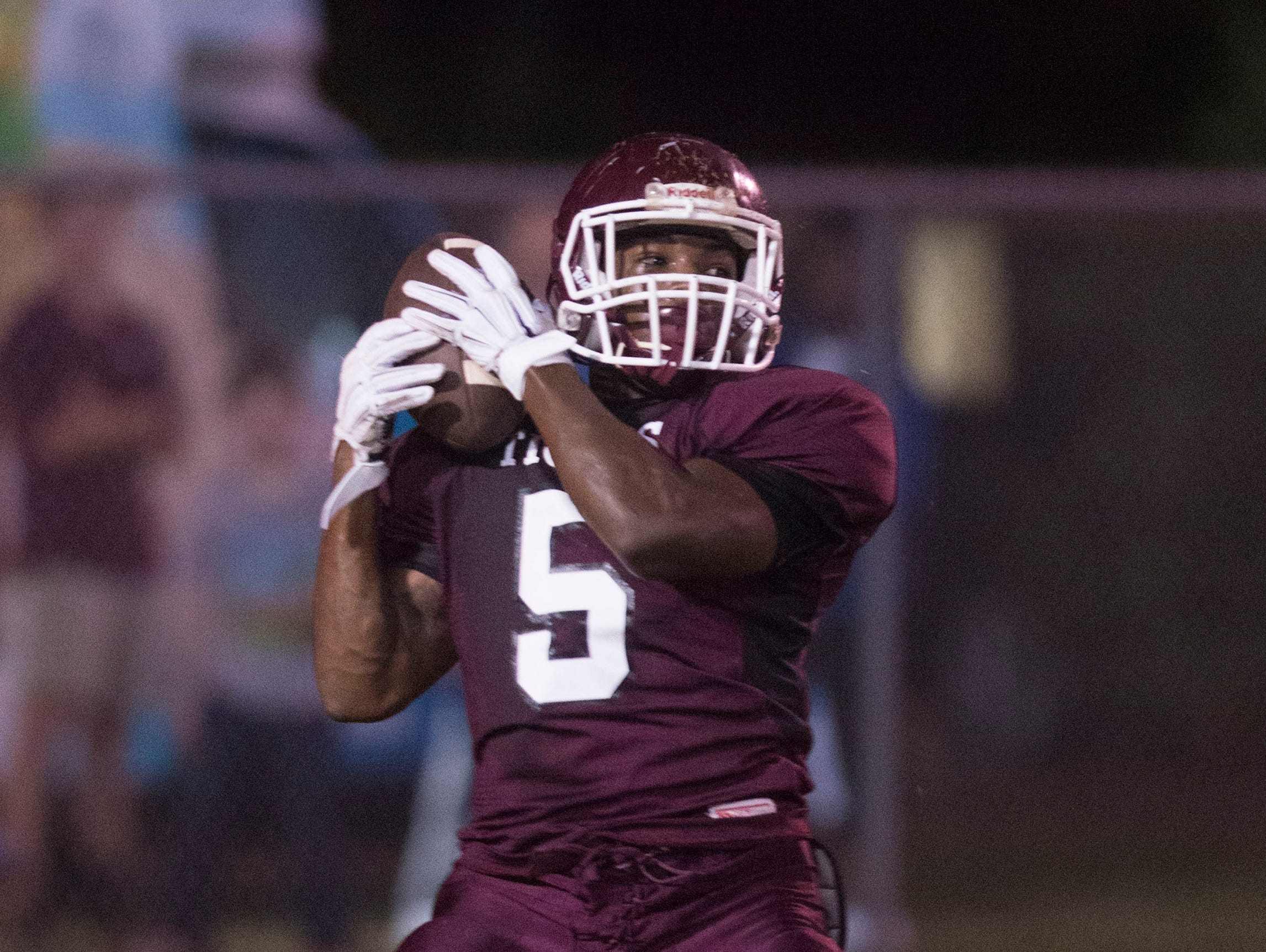 Pensacola High School's Boston Robinson, fight for mishandles a kickoff during Friday night's preseason opener against Tate High School Friday night.
