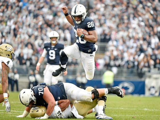 Penn State's Saquon Barkley leaps over teammate Brendan Mahon and Akron's Deon'Tae Moore in the first half of an NCAA Division I college football game Saturday, Sept. 2, 2017, at Beaver Stadium. Penn State, fresh off a Big 10 Championship win, shut out Akron 52-0 in its season opener.