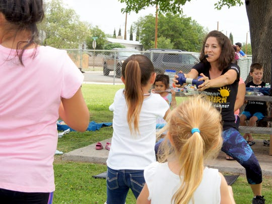 Raquel Quintana manages to keep the attention of her young exercise pals through music, song and dance during Luna County's Healthy Kids Summer Burn Fitness program at city parks.