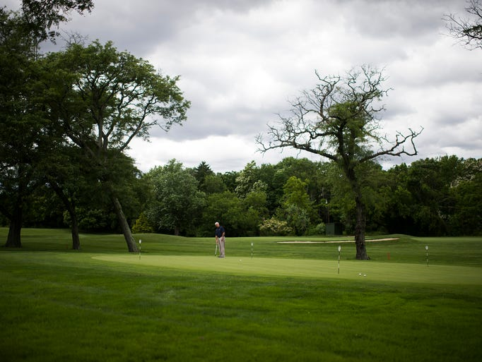 A golfer practices his putting following an unveiling