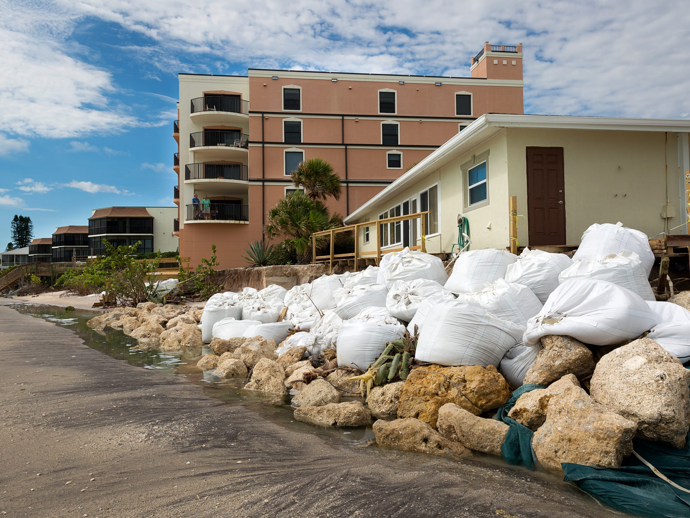 Sand bags and other attempts to slow erosion sit scattered
