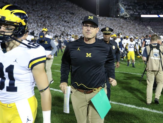 Michigan head coach Jim Harbaugh leaves the field after