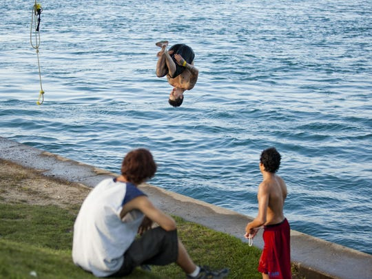 Tyler Hamilton, 20, of Port Huron, does a front flip into the St. Clair River during Rockin' the Rivers Thursday at Kiefer Park in Port Huron.