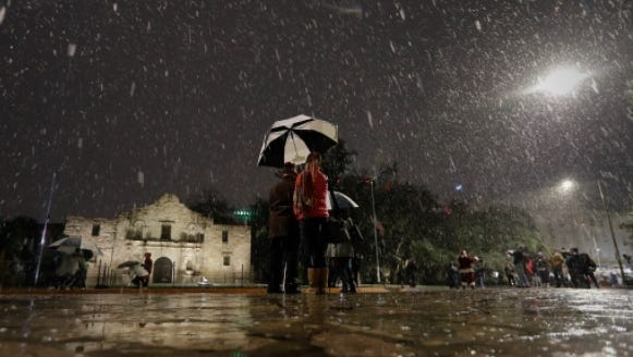 Visitors walk near the Alamo as snow falls in downtown San Antonio,  Dec. 7, 2017. The National Weather Service said up to 2.5 inches of snow had been measured in the San Antonio area. The most recent comparable snowfall in San Antonio was in January 1987, when 1.3 inches of snow accumulated.