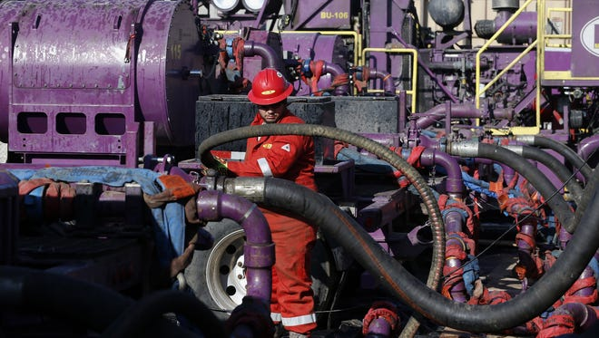 A worker adjusts hoses during a hydraulic fracturing operation March 25 at an Encana gas well near Mead, Colo.