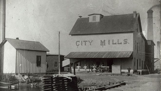 Workers stand in front of the City Mills in Neenah in this photograph from 1895.