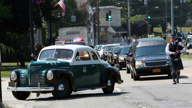 An antique New York City police car leads the funeral procession for retired NYPD Sgt. Jimmy O'Neill at Saint James church in Carmel on Friday.