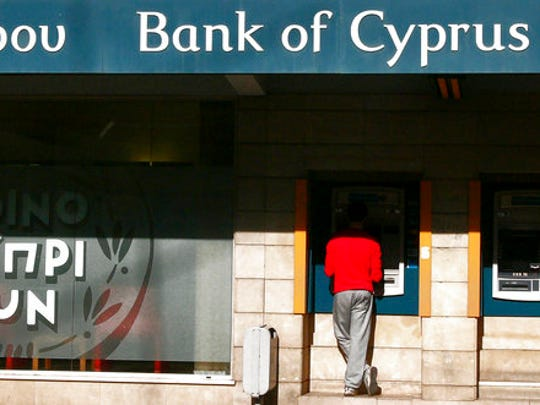 FILE - In this Oct. 30, 2013, file photo. a man uses an ATM machine outside of a branch of Bank of Cyprus in capital Nicosia, Cyprus.  U.S. Treasury Department agents have recently obtained information about offshore financial transactions involving President Donald Trump's former campaign chairman, Paul Manafort, as part of a federal anti-corruption probe into his work in Eastern Europe, The Associated Press has learned. Information about Manafort's banking transactions was turned over to U.S. agents working in the Financial Crimes Enforcement Network, a Treasury Department bureau, by the Unit for Combating Money Laundering in the Mediterranean country of Cyprus, a person familiar with the case said, speaking on condition of anonymity because the person was not authorized to publicly discuss an ongoing, global criminal investigation.