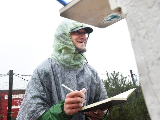 Winter time through hiker Justin Lichter signs the official trail register book after arriving at the southern terminus of their historic journey on the Pacific Crest Trail at the Mexican border near Campo, Calif. on March 1, 2015.