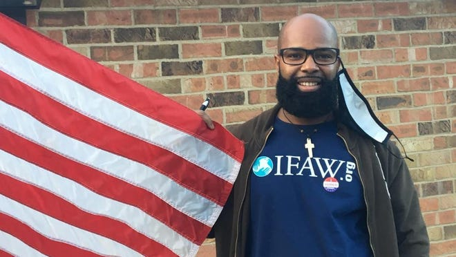New Bedford resident Adilson Cabral holds the American flag outside Hillside Court polling station after voting for the first time Tuesday in the presidential election.