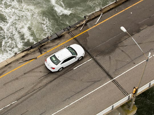 A vehicle sits on the road by a missing section of guard rail along a segment of the Chesapeake Bay Bridge-Tunnel where a tractor-trailer went over the southbound side at the 15-mile marker, Thursday afternoon Feb. 9, 2017, near Virginia Beach, Va.