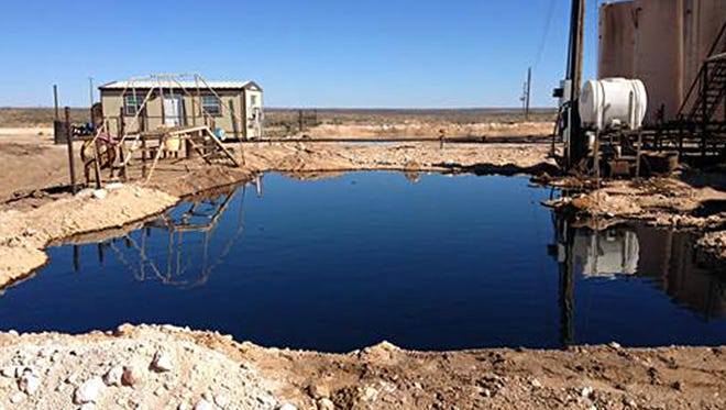 This Tuesday, March 8, 2016 photo provided by the New Mexico State Land Office shows an oil-and-water mixture on the ground at a waste-water disposal site serving the oil and gas industry outside Eunice, N.M. The State Land Office wants the Midland, Texas-based company Siana Operating LLC to stop water deliveries and clean up the site.