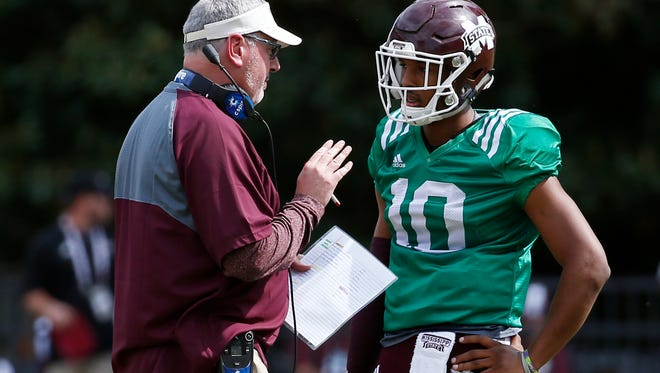 Joe Moorhead, left, confers with Maroon quarterback Keytaon Thompson (10) during the first half of Mississippi State's Maroon and White spring NCAA college football game, Saturday, April 21, 2018, in Starkville, Miss. (AP Photo/Rogelio V. Solis)