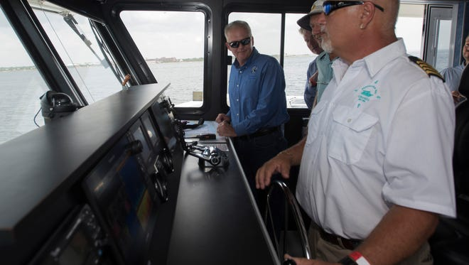 Capt. George Aswad, right, takes the helm of the Pelican Perch ferry and gives Escambia County Commissioner Jeff Bergosh an overview of the operation during a media event Wednesday, June 20, 2018.