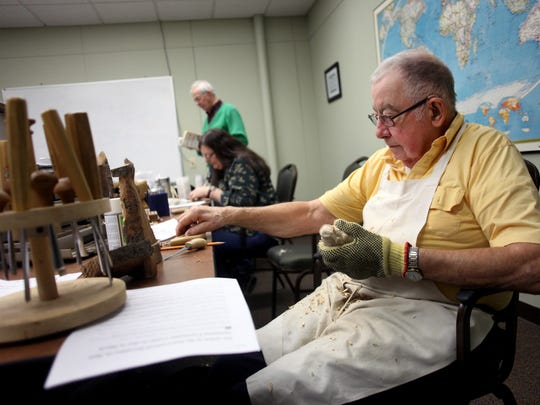 Ed Kraus picks up a new tool as he works on carving