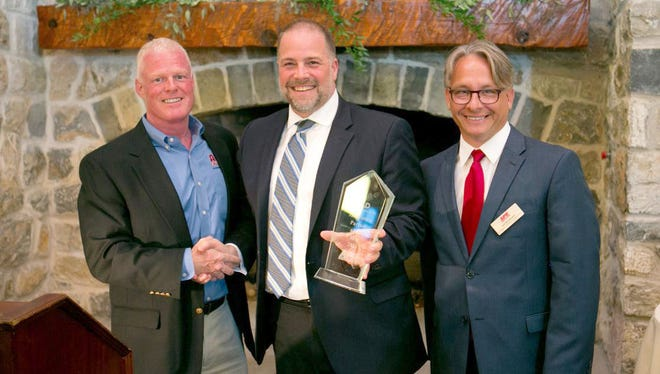 """At its annual awards dinner in Hershey last month, APR Supply Co. named Affiliated Distributors its Innovation Partner of the Year. Scott Weaver, left, APR president and CEO of APR, presents the award to Justin Dunscomb, HVAC divisional vice president of AD. Also pictured is Jeff MacDowell, vice president of marketing and emerging markets at APR. In his presentation, Weaver noted that """"AD offers support in accelerated growth, sales and marketing programs, brand advocacy, HR services and ecommerce, combined with strong service and support."""""""