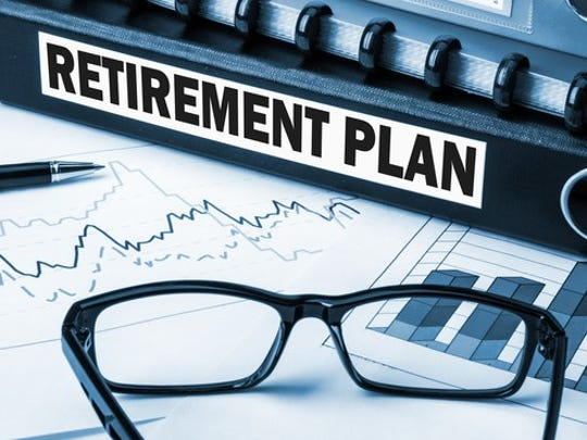 """binder labeled """"retirement plan"""" with charts and tables on a desk."""