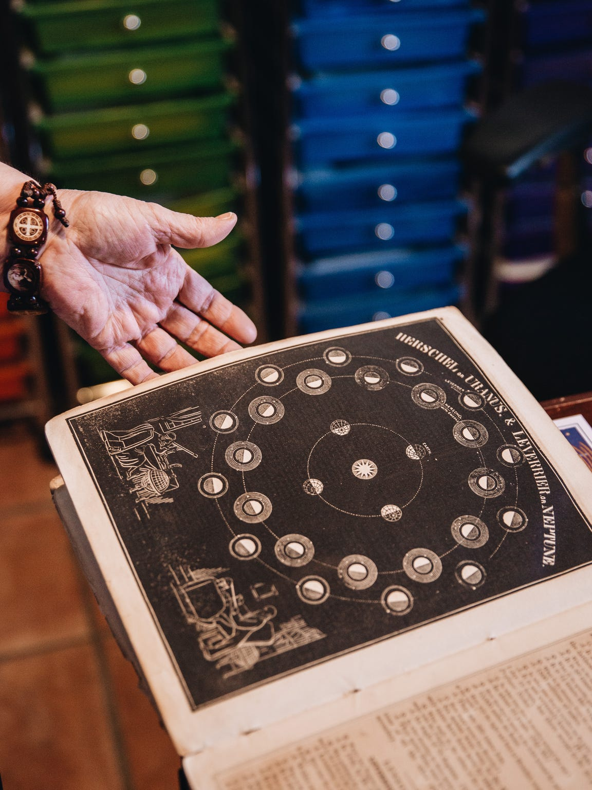 Dana Haynes opens an astrology book in her home.
