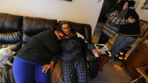 Chris Chronister Jr. embraces his mother Karen, right, as his girlfriend Darby Frey hugs his father Chris Sr. on the couch in a neighbor's home in Wrightville on Friday, Feb. An early morning fire chased the Chronister's from their home in Wrightsville on Friday, Feb. 27, 2015.  Jason Plotkin - Daily Record/Sunday News