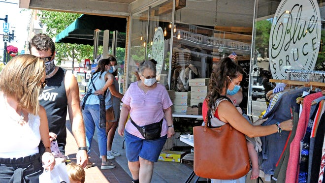 "Shoppers took advantage of deals during the inaugural ""Christmas in July Sidewalk Spectacular"" event Saturday."