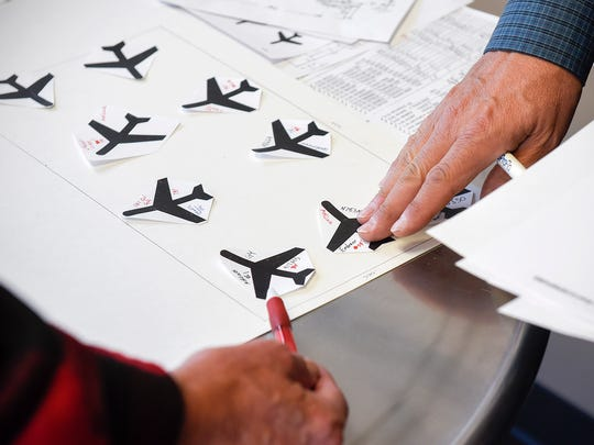 The staff at St. Cloud Aviation use a scale model of the site and planes Wednesday, Jan. 31, to organize more than 60 large planes that will park there during Super Bowl weekend.