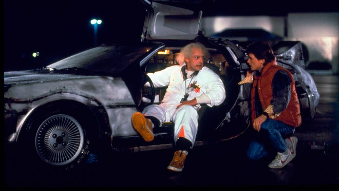 """Christopher Lloyd, left, as Dr. Emmett Brown, and Michael J. Fox as Marty McFly in the 1985 film, """"Back to the Future."""" Wednesday's so-called """"Back to the Future"""" Day marks the date - Oct. 21, 2015 - that characters McFly, Brown and Jennifer Parker famously journeyed to the future in the film trilogy's second installment in 1989."""