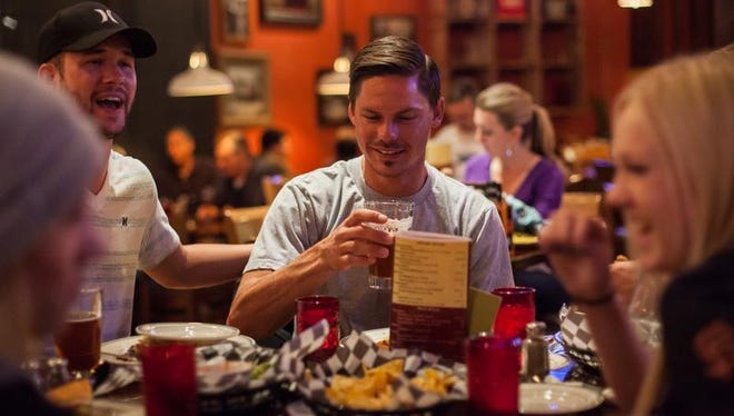 """Chad Seegmiller and David Barnard dine with friends at George's Corner Restaurant in downtown St. George in this 2014 file photo. The restaurant is one of many that prepare alcohol in a back room in keeping with Utah's """"Zion Curtain"""" law to prevent family-friendly businesses from making alcohol drinks within view of young diners, although a bill awaiting the governor's signature may ease the restrictions on the industry."""