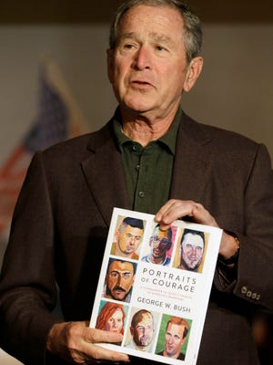 Former President George W. Bush holds a copy of his new book, 'Portraits of Courage,' in Dallas on Feb. 28, 2017.